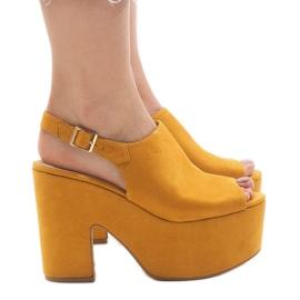 Sandali gialli su un enorme mattone 8263CA giallo